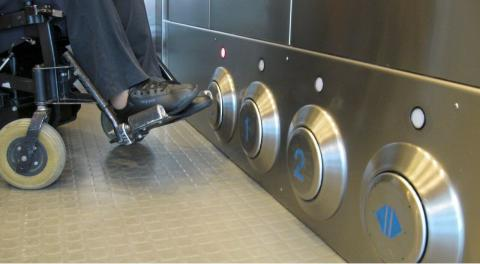 A wheelchair user rolls-up to buttons that are low to the ground inside an elevator to selected their desired floor