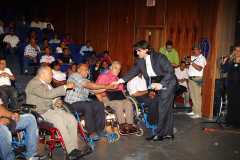 A man wearing a suit and holding documents shakes hands with four men using wheelchairs in an auditorium.