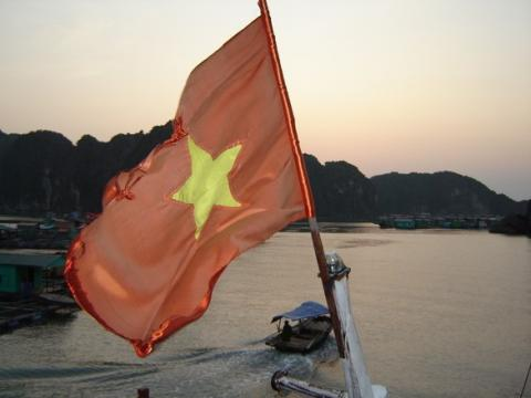 A red flag with a yellow star in the center flies high over a boat.
