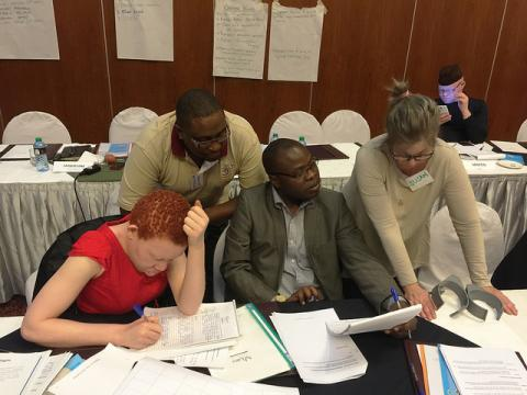 Three Kenyan and one US professional look at paperwork together at a table. One person uses crutches and one person appears to have albinism.