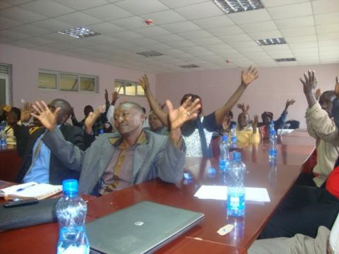 Adults seated at tables, all facing in the same direction, raise their arms high in the air.