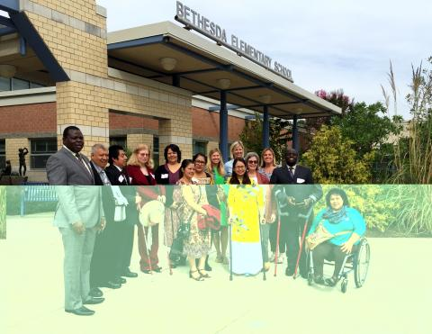 A diverse group of people, some with and some without disabilities, pose for a photo in front of the front of a school. A sign above the entrance reads Bethesda Elementary School.