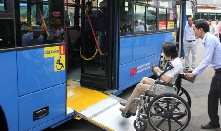 A women using a wheelchair enters a bus on a ramp and a companion pushes her wheelchair.