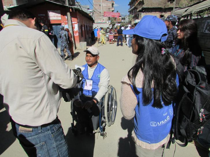 In a dusty street, a man using a wheelchair is wearing a blue vest and is talking to reporters holding video cameras.