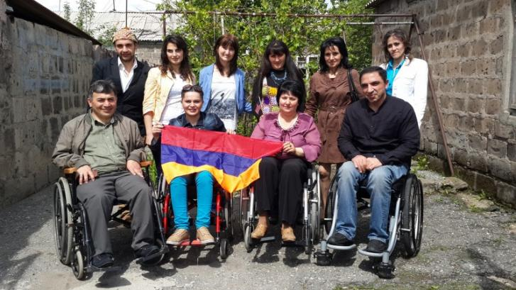 A group of 10 smiling men and women with and without disabilities hold the Armenian flag on a sidewalk. The front row includes four people using wheelchairs and the back row from includes six people standing.