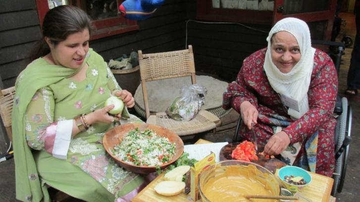 A woman who is blind and woman using a wheelchair sit at a table to chop vegetables.