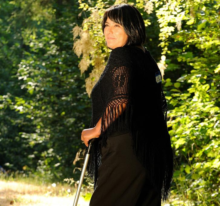 A woman dressed in black stands in a sunny forest. She looks over her shoulder and holds a cane in one hand.