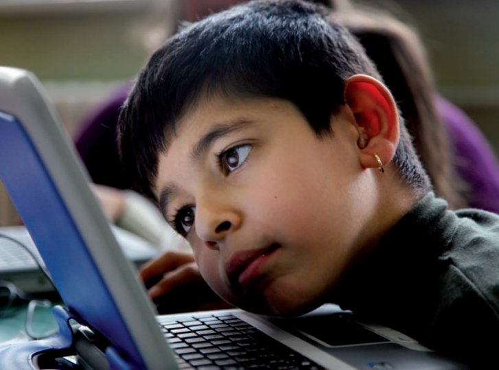A picture of a young child with short hair and an ear ring, leaning very close to see their laptop screen.