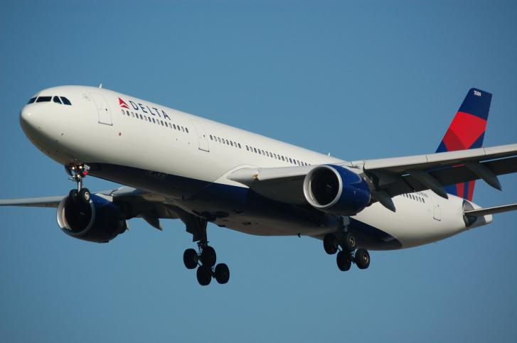 A Delta Airlines airbus in flight across a blue sky