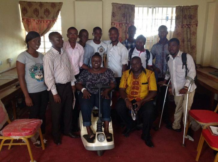 Two women and ten men stand in a group. Several of them have physical disabilities and use equipment such as a scooter, cane, and crutches.
