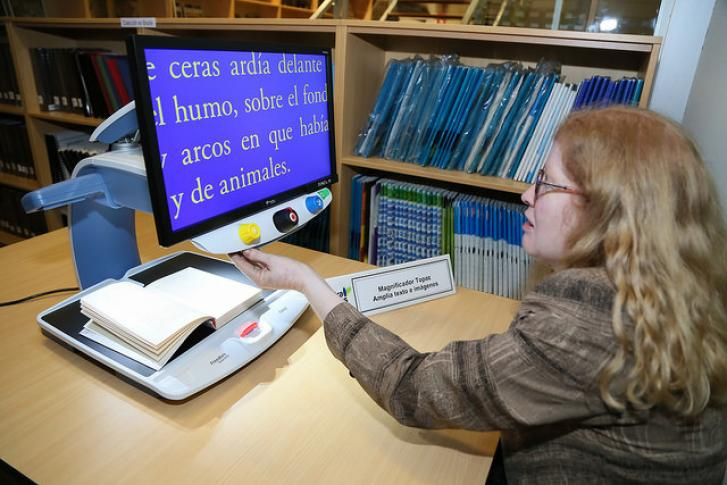 A women sits at a desk in front of a text magnifier machine. She puts an open book face-up on the machine, which reflects the text onto a monitor in large print. She is able to read the large text on the monitor screen.