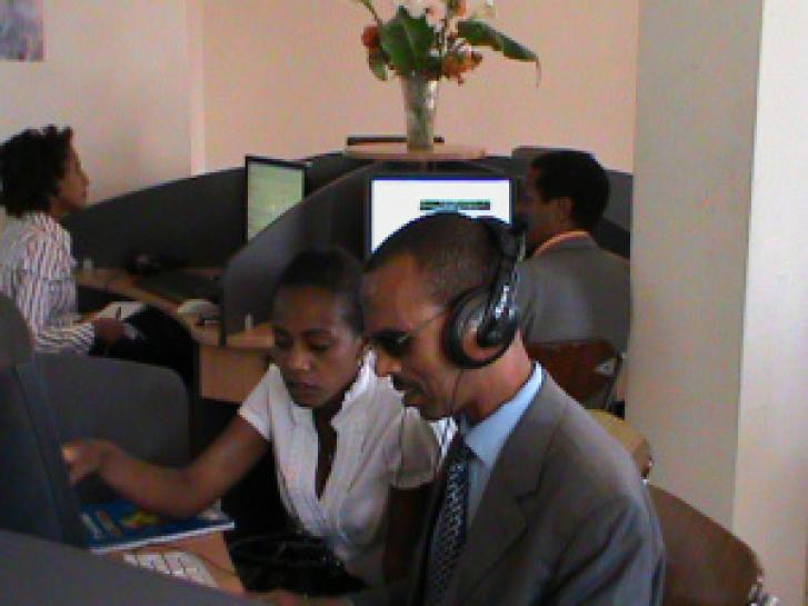 In the foreground is a blind man with headphones, sharing the same computer terminal with a sighted woman who is looking at the screen over his shoulder. Behind them are two more people working individually at another two computer terminals, neither of them are using headphones.