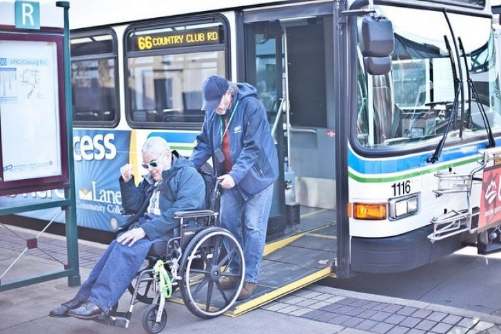 A man using a wheelchair exits a bus on a ramp with the help of a friend who pushes his wheelchair