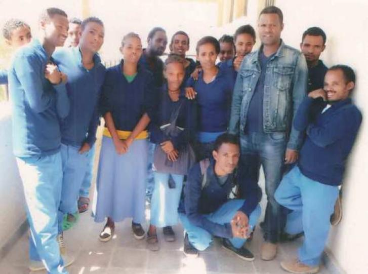 A man stands with a group of young men and women who all wear dark blue tops with light blue pants