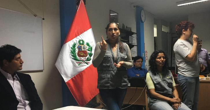 A woman using sign language is in an office setting with other people from Peru. A large flag of Peru with red stripes on the sides and white in the middle is featured behind her.