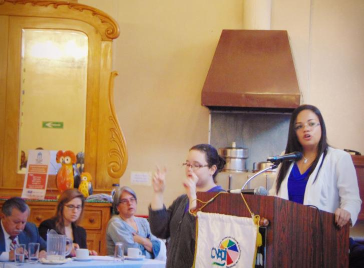 Flor stands at a podium speaking to a group of seated people. A Sign Language interpreter stands next to the podium and interprets her words.